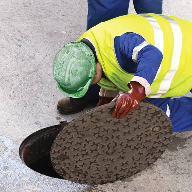 worker opening sewer manhole cover