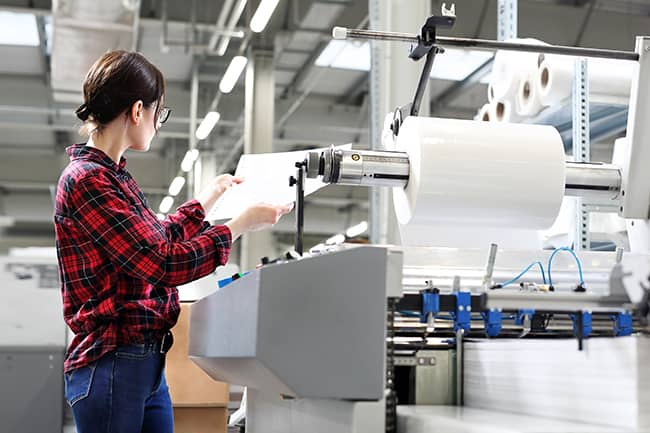 Woman inspecting ream of paper